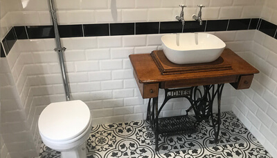 Toilet and pedestal sink with white tiled walls